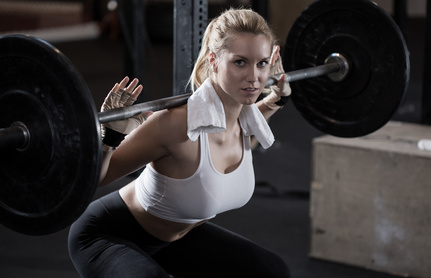 Image of girl making squat with barbell