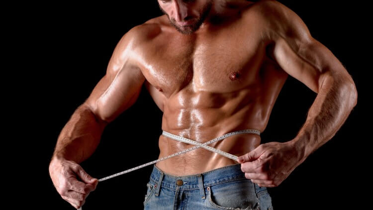 Bodybuilder avec ruban à mesurer autour de la poitrine