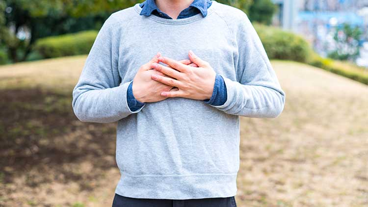 homme dans un sweat-shirt posant dans un parc