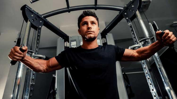 homme dans une salle de sport travaillant sur ses muscles des bras