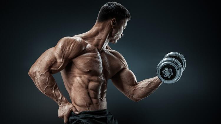 Bodybuilder faisant biceps curl avec la main sur la hanche
