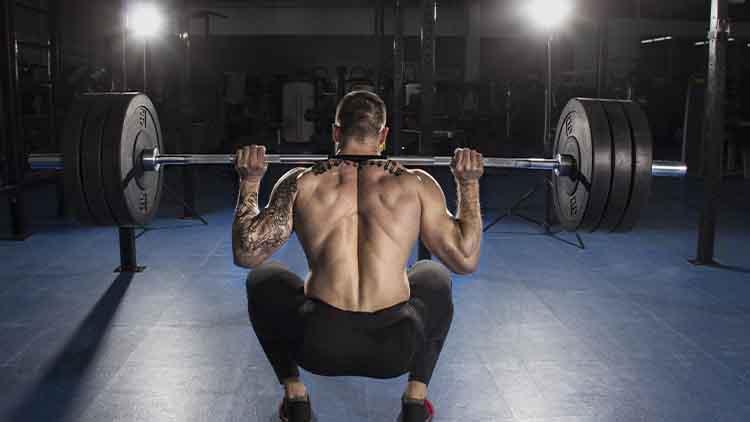Bodybuilder musculaire attrayant faire des exercices de squat lourd