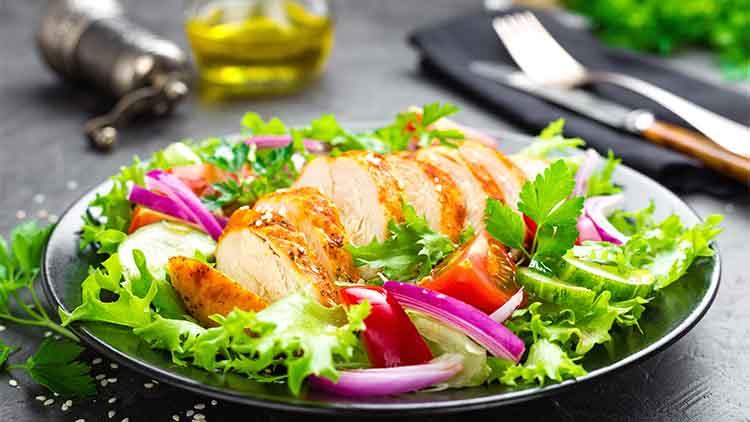 Salade de légumes frais avec une poitrine de poulet.