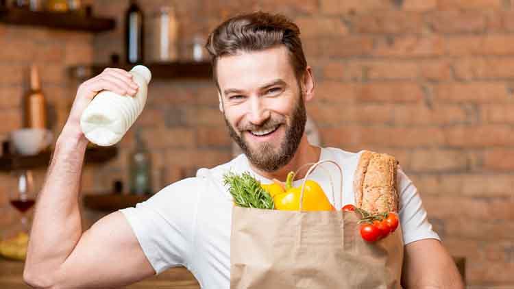 Bel homme tenant le lait avec un sac en papier rempli d'aliments sains dans la cuisine