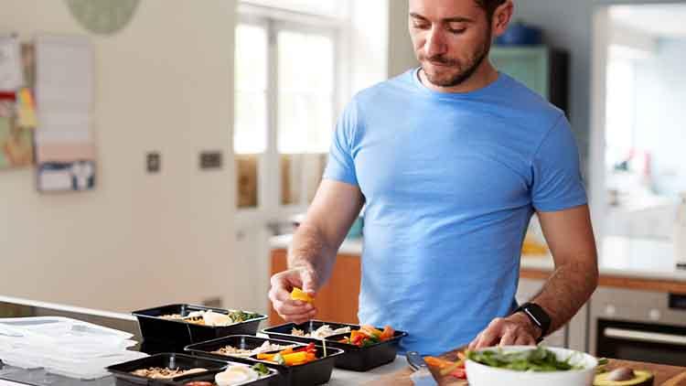 Homme prépare des repas sains à la maison dans la cuisine