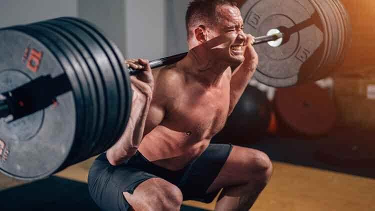 Homme musclé, formation de squats avec haltères aux épaules.