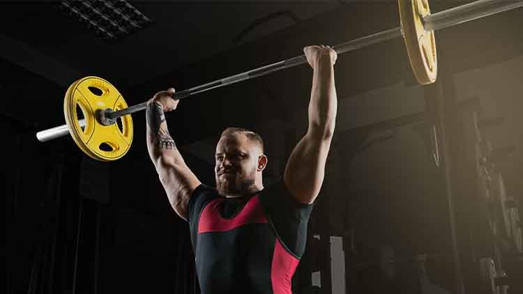 Powerlifter professionnel lève la barre au-dessus de sa tête dans un squat