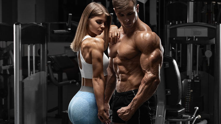 Sportive couple sexy montrant le muscle et l'entraînement dans la salle de gym