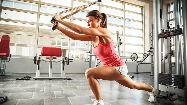Jeune femme avec un corps de sport fait la séance d'entraînement à la gym.
