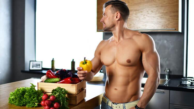 homme musclé sport debout dans la cuisine avec épicerie légumes tenir poivron jaune dans les mains en regardant le coin souriant