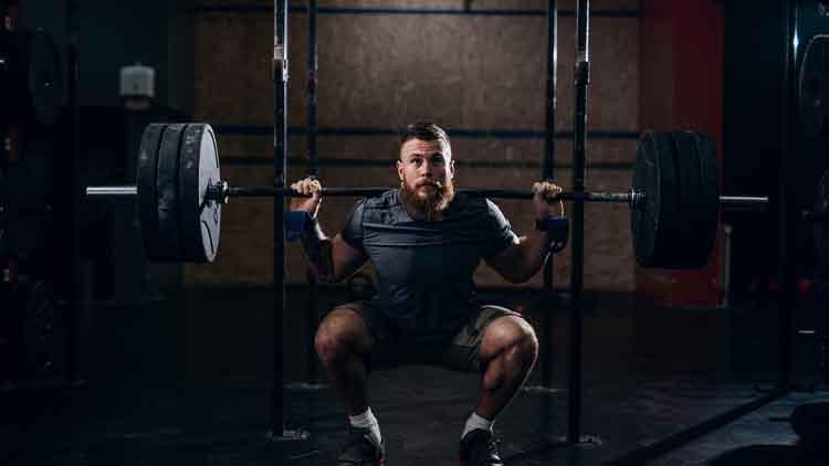 Homme barbu caucasien musclé, soulever des poids et faire squat arrière dans la salle de gym.