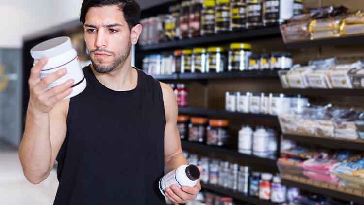 Jeune sportif musclé à la recherche de suppléments dans le magasin