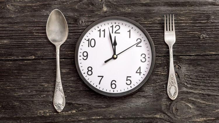 Horloge avec une fourchette et une cuillère sur une surface en bois