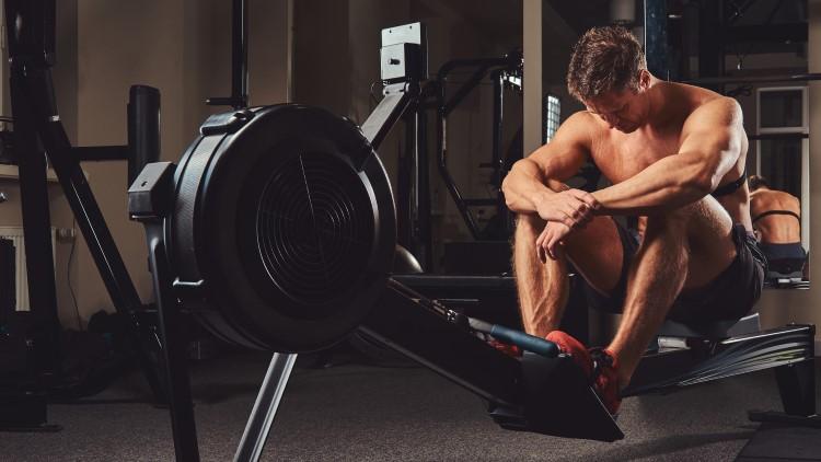 Athlète musculaire se reposant sur la machine à ramer dans la salle de gym