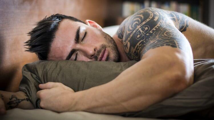 Homme musclé tenant des draps endormis
