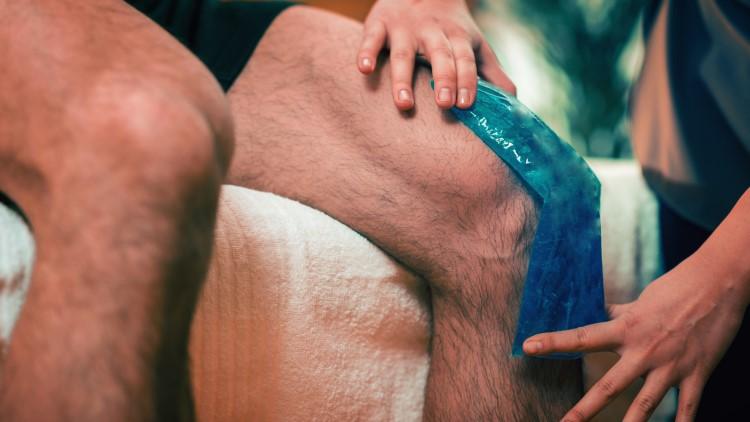 Personne appliquant un coussinet anti-douleur au genou sur le genou de l'homme